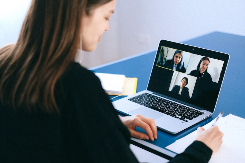 Professional woman using videoconferencing tips while on a three-way call.
